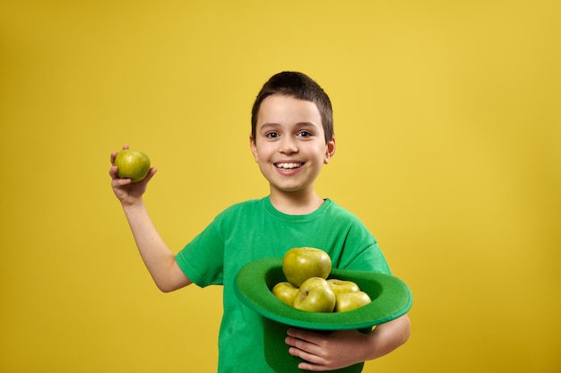 面白い小さな男の子は黄色の表面に孤立して立って、片方の手にリンゴともう片方の手に青リンゴでいっぱいのアイルランドのレプラコーン帽子を持っています