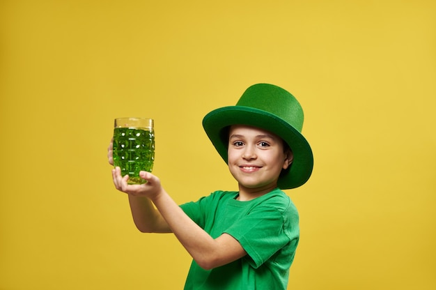 레프 러콘 요정 아일랜드어 녹색 모자를 쓰고 재미있는 어린 소년이 카메라에 녹색 음료와 미소로 유리를 보유하고 있습니다.
