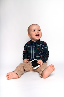 Funny little boy with a phone on a white background