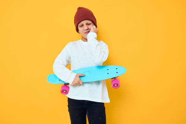 Funny little boy with red backpack blue skateboard childhood lifestyle concept