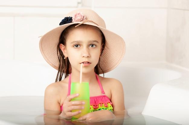 帽子をかぶった面白い小さな白人の美しい女の子は家でビーチ入浴をします