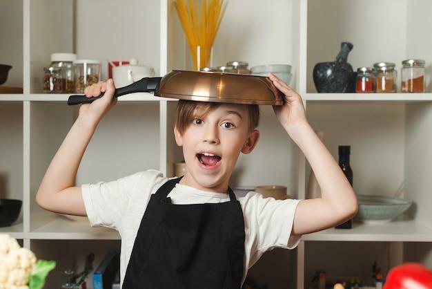 부엌에 팬이 있는 재미있는 작은 요리사. 요리사 앞치마를 입은 소년. 미래의 직업을 꿈꾸는 아이. 요리 교실에서 아이입니다. 어린이, 요리 교실 및 라이프 스타일 개념.