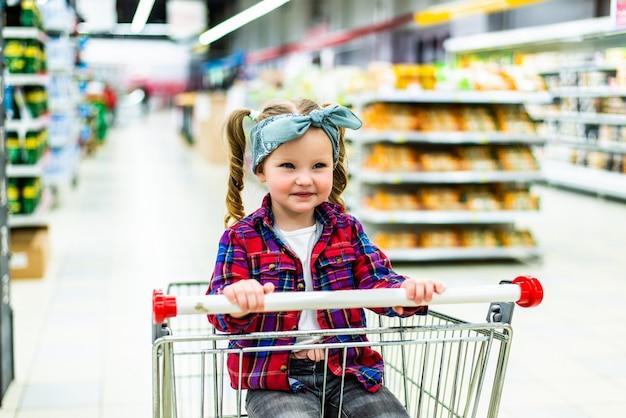 Забавная маленькая девочка, сидящая в тележке во время семейных покупок в гипермаркете