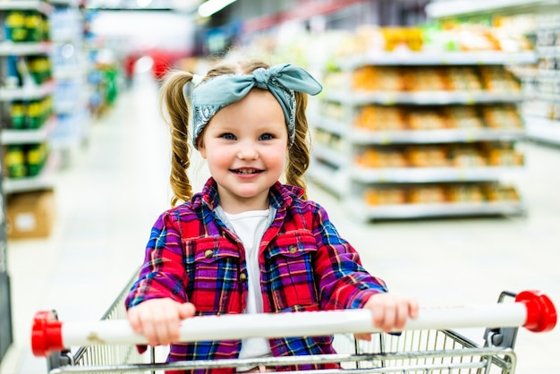 Funny little child girl, sitting in the trolley during family shopping in hypermarket