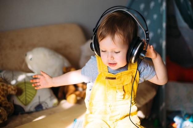 家の肖像画でヘッドフォンで楽しんでいる面白い小さな子供