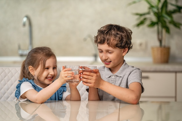 Funny little children drink water in the kitchen at home.