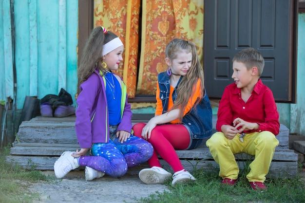 90年代のスタイルに身を包んだ明るい化粧の面白い小さな子供たちの女の子