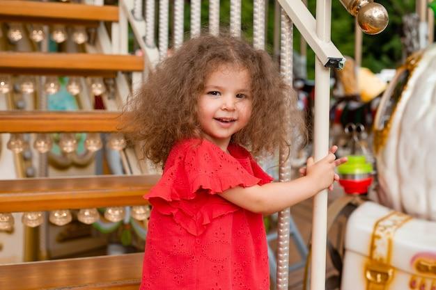 Забавная маленькая фигурная девочка в красном платье на лестнице с фонариками