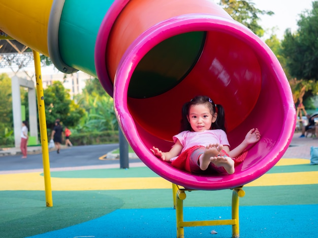Funny little cute girl playing slide at the playground.