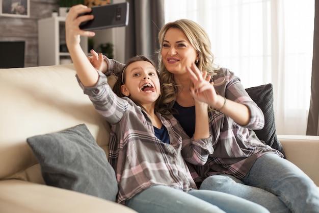 面白い小さな娘と彼女の母親は、スマートフォンを使用して自分撮りをしています。幸せな子供。