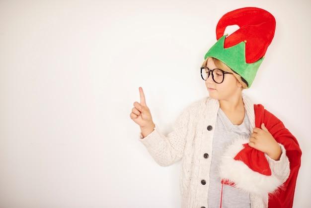 Piccolo elfo divertente che mostra sulla parete vuota bianca