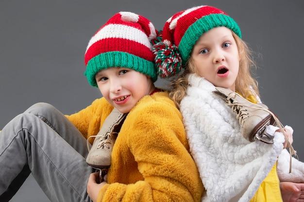 Смешная маленькая девочка и мальчик в вязаных рождественских шапках и старинных коньках