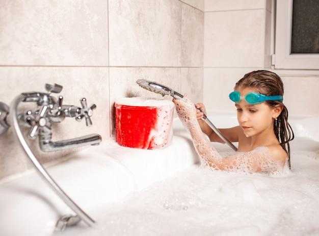 재미있는 어린 소녀는 욕조에서 목욕하고 샤워에서 하얀 거품에 물을 부어