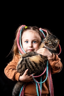 Funny little girl on a black background with afro elastic bands, pigtails on elastic, holding a cat with bulging eyes cool