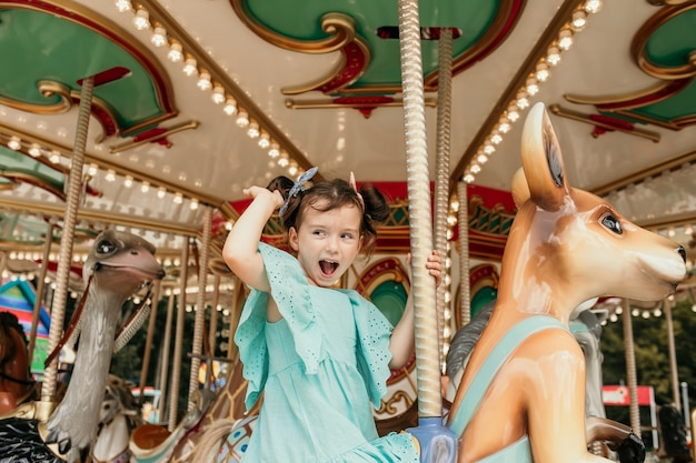 Funny little girl in a blue dress rides on an amusement park ride