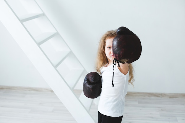 Funny little girl in boxing gloves. winner.