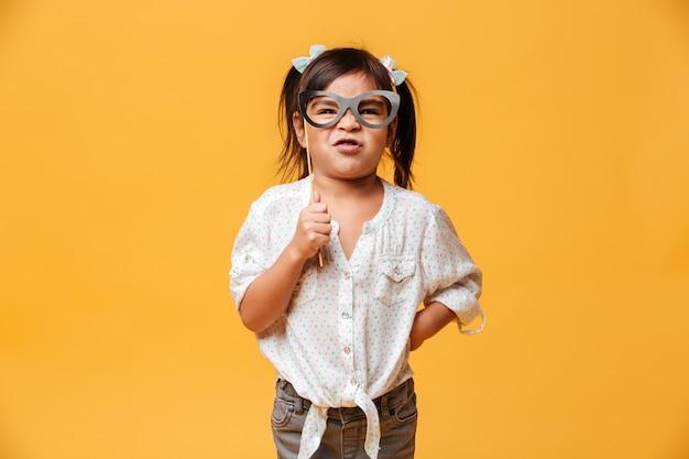 Funny little girl child holding fake glasses.