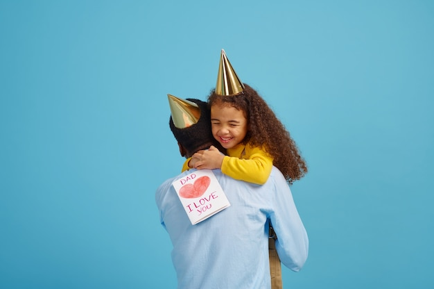 Funny little girl congratulates her father. pretty child hugs her dad. happy fathers day