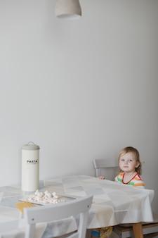 Смешная маленькая девочка, готовящая макароны на кухне