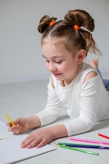 Забавная маленькая девочка рисует в альбоме цветными карандашами домашнее образование детский сад