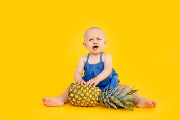 Funny little girl dressed in blue dress sitting and playing with pineapple isolated on yellow