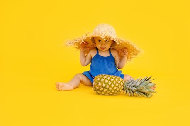 Смешная маленькая девочка в синем платье сидит и играет с ананасом, изолированным на желтом