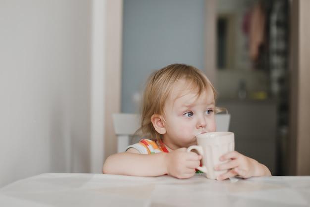 Смешная маленькая девочка пьет молоко, сидя на кухне