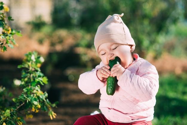 春に庭で新鮮なキュウリを食べる面白い女の子