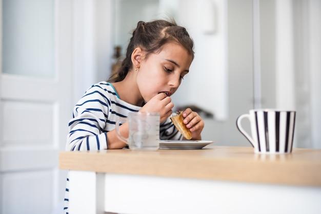 手作りのクッキーを食べる面白い女の子