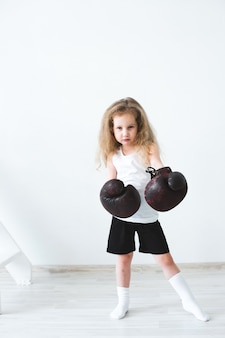 Funny little girl female wearing boxing gloves.