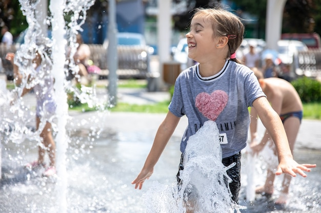 Funny little girl in a fountain, among the splashes of water on a hot summer day.