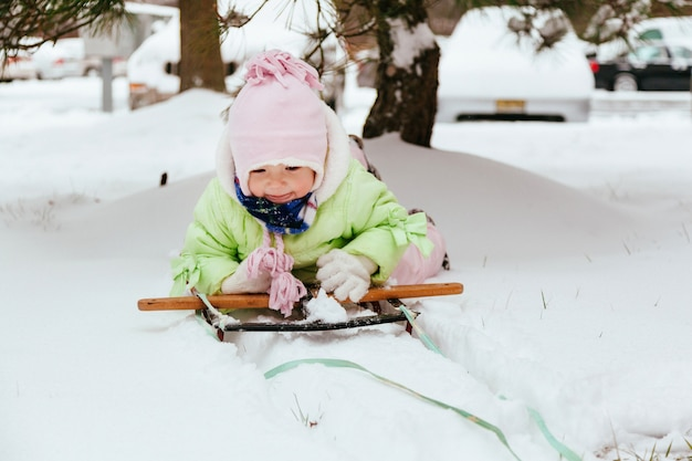 Funny little girl having fun in beautiful winter park during