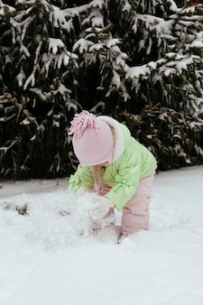 Смешная маленькая девочка с удовольствием в красивом зимнем парке во время снегопада
