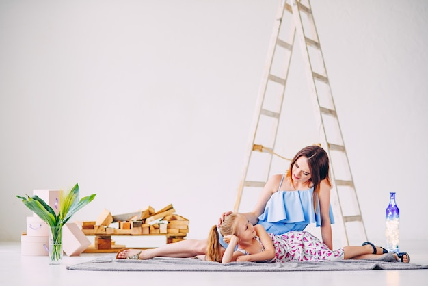 Забавная маленькая девочка, весело проводящая время с ее мамой в белой украшенной комнате. пустая копия пространства, свободное место для текста.