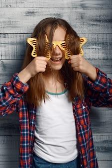 Funny little girl in headphones and star glasses