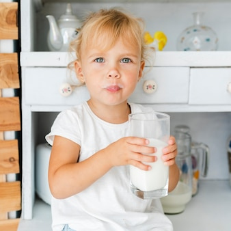 Funny little girl holding a glass of milk