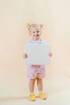 Funny little girl holds a sign for inscriptions. light background