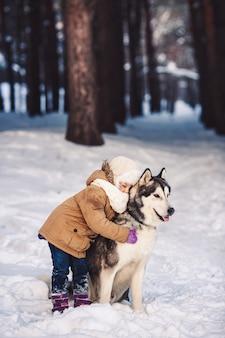 Забавная маленькая девочка обнимает свою большую собаку маламут зимой в лесу