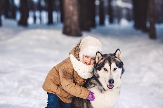 Забавная маленькая девочка обнимает свою большую собаку маламут зимой в лесу Premium Фотографии