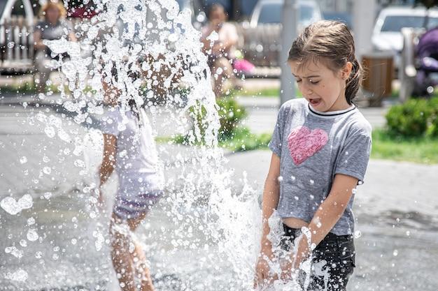 暑い夏の日の水しぶきの中で、噴水の面白い少女。