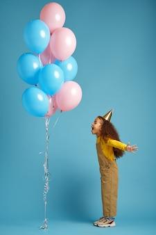 キャップの面白い小さな女の子は、カラフルな風船、青い背景の束を保持しています。かわいい子供がサプライズ、イベント、誕生日パーティーを開催しました