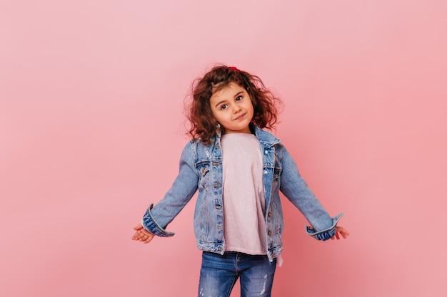 멀리보고 데님 재킷에 재미있는 어린 소녀. 분홍색 배경에 고립 된 매력적인 초반 아이의 스튜디오 샷.