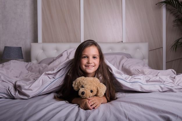 ぬいぐるみでベッドに横たわっているパジャマの面白い女の子