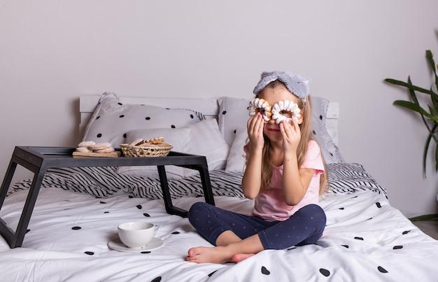 パンのトレイとベッドに座っているパジャマの面白い女の子