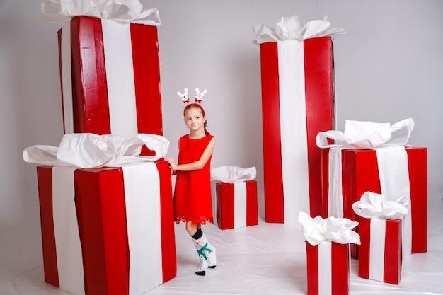 Забавная маленькая девочка в новогоднем образе, демонстрирующая разные эмоции.