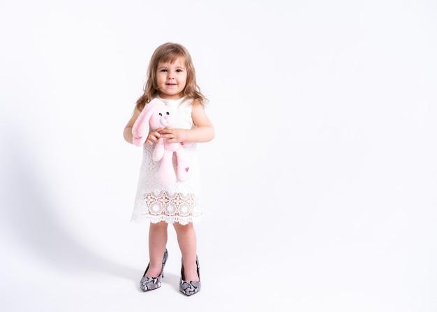 Смешная маленькая девочка в белом платье пытается ее мать обувь с каблуками на белой поверхности.