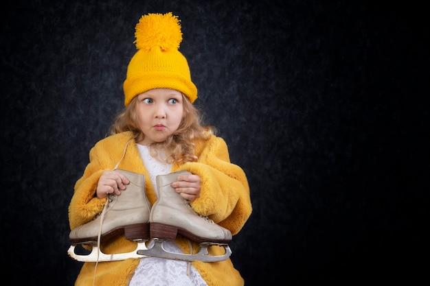 Смешная маленькая девочка в зимней одежде с коньками.