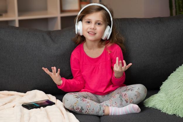 춤과 리듬으로 이동 무선 헤드폰에서 재미있는 작은 소녀. 헤드폰을 착용하는 어린 소녀. 헤드폰에서 아이. 헤드폰으로 음악을 듣고 행복 한 어린 소녀