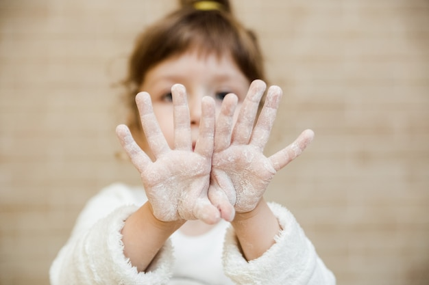 Funny little girl is covered in flour.children chef concept.close up
