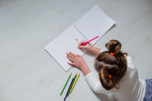 Смешная маленькая девочка лежит на деревянном полу и рисует в альбоме цветными карандашами